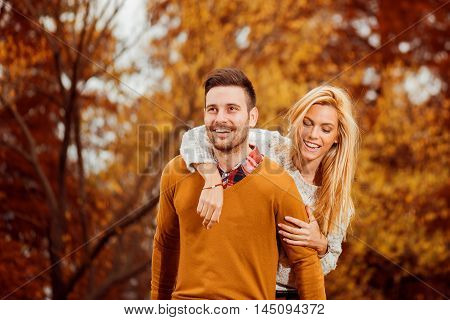 Couple in the autumn park.Smilling man and woman outside.