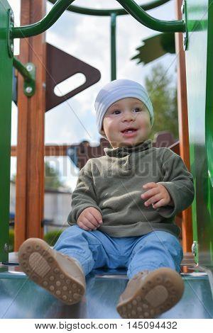 Happy little toddler boy having fun sliding on playground.