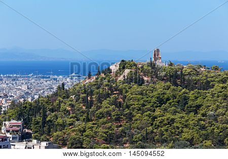 View on the Philopappos Monument on top of Mouseion Hill from the Acropolis of Athens Greece