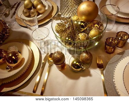 Golden Christmas table setting and festive centrepiece