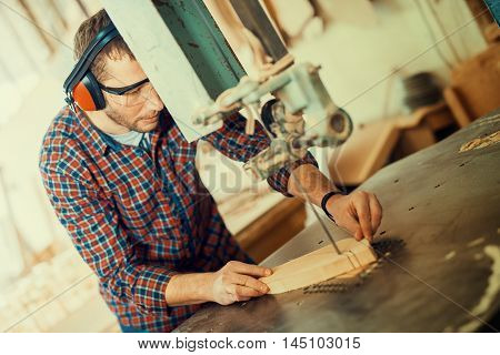 Close up of a young carpenter at work.He is using a bandsaw also known as a jigsaw or a scroll saw cuts through a piece of wood.
