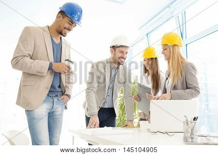 Architect looking over building plans with construction workers.Construction workers checking the architectural plans before they start the building project.
