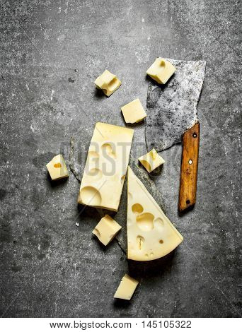 Hatchet and pieces of fresh cheese on the stone table.