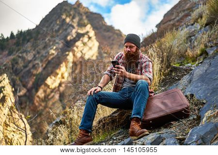 bearded guy lost in the mountains looking on phone for directions