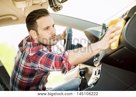 Young man cleaning his car outdoors.Man cleaning the dashboard of his car.