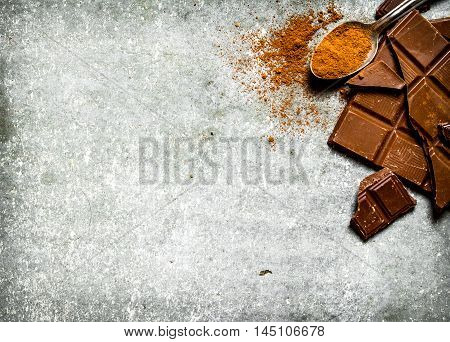 Chocolate with cocoa powder in the spoon. On the stone table.