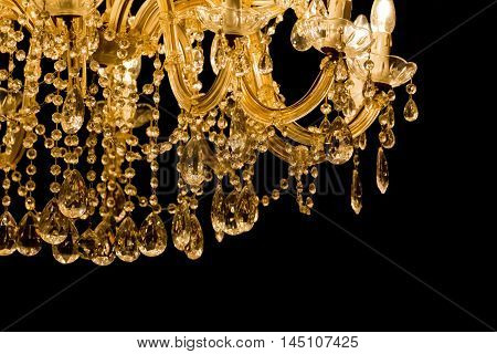 Luxury chandelier with light candles and right dark background. Noble candelabra hanging on ceiling with lots of little gems.