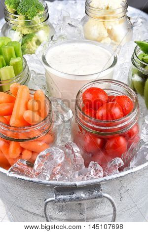 Fresh vegetables in canning jars an ice bucket for a healthy picnic snack. Closeup in vertical format.