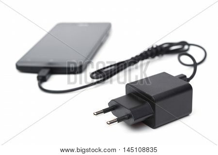 Mobile phone and adapter charger isolated on white