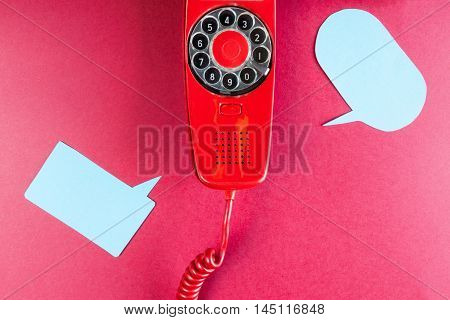 Vintage red phone and speech ballons on red background