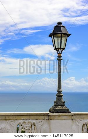 Urban Lamppost on ancient wall with the sea in the background in the city of Salvador Bahia