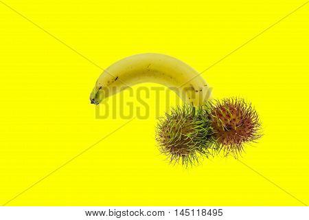 Banana and rambutan isolated on yellow background (parody image)