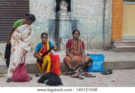 Madurai India - October 19 2013: Three women sell black human hair out of bags while sitting on the sidewalk near the Meenakshi Temple. All wear saris.