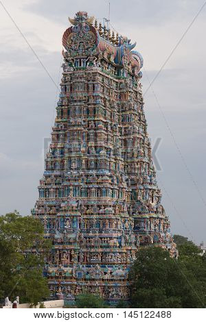 Madurai India - October 19 2013: Closeup of East Gopuram of the Meenakshi Temple: the North and West sides of the tower. Levels of pastel colored statues.