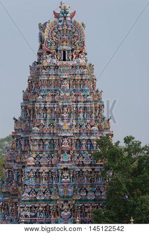 Madurai India - October 19 2013: Closeup of one Vimanam of the Meenakshi Temple against bluish skies. Pastel colors and abundance of statues.