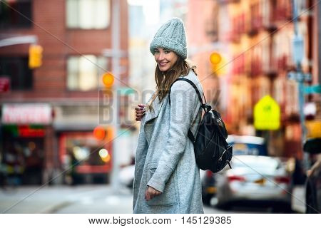 Beautiful happy woman walking on the city street wearing casual greay coat and hat with a bag