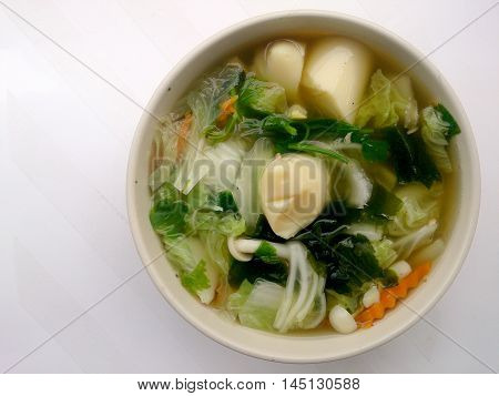 Clear Soup With Bean Curd , Mix Vegetable, Tofu And Seaweed In White Bowl On White Background. Veget