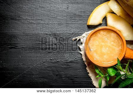 Melon pulp in a bowl with branches of mint. On the black wooden table.