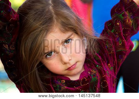 An irritated little girl gives an intense look. She has her arms up and is leaning on something with her head cocked to the side looking at the viewer with a furrowed brow and intense eyes.