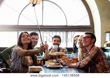 people, leisure, friendship and technology concept - happy friends taking picture by smartphone selfie stick, drinking beer and eating snacks at bar or pub