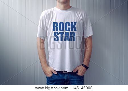 Casual adult male wearing t-shirt with Rock Star title man in jeans leaning on the wall