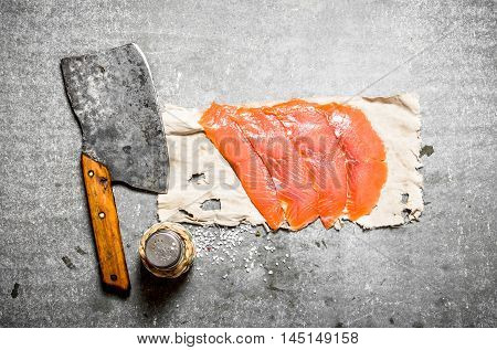Thinly sliced smoked salmon with a hatchet and salt. On a stone background.