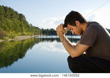 Man praying and meditating by beautiful lake