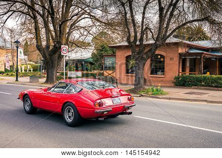 Adelaide Australia - August 13 2016: Red Ferrari 365 GTB 4 Daytona driving on the main street in Hahndorf on a day