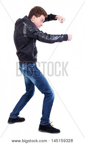 back view of guy funny fights waving his arms and legs. Curly guy in a black leather jacket funny fights