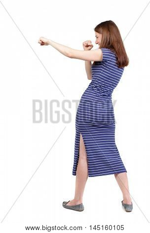 skinny woman funny fights waving his arms and legs. brunette in a blue striped dress stands sideways and hit a hand ..