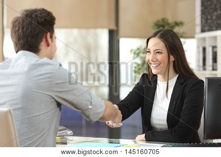 Happy businesswoman handshaking with client closing deal in an office interior with a window in the background