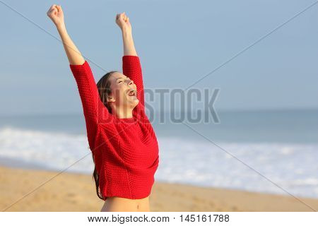 Happy funny excited woman wearing red color sweater raising arms euphoric on the beach at sunset with a warm light in the background