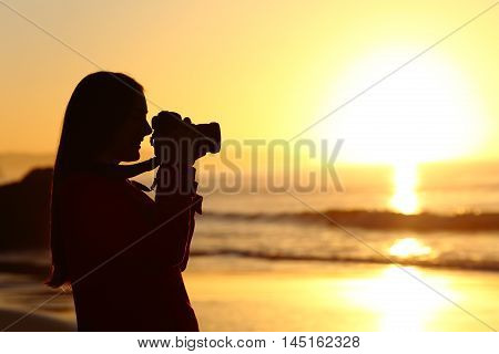 Side view of a backlit photographer silhouette photographing sun with dslr camera at sunrise on the beach with the ocean in the background