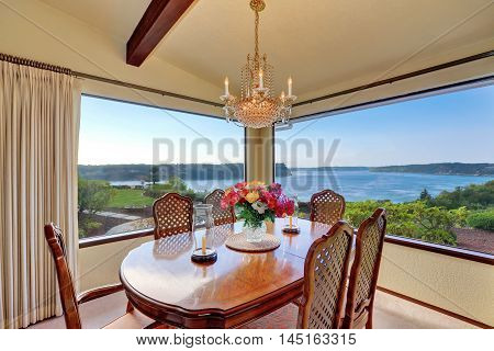 Dining Room With Carved Wood Table Set And Water View