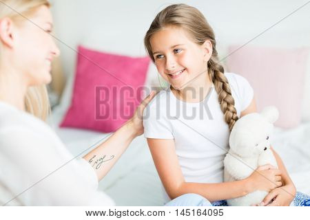 Happy girl with teddybear looking at her mother