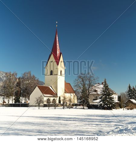 Winter view of the church of Thoerl-Maglern (Pfarrkirche St. Andreas) with snow and the  Alps in the background, Arnoldstein, Austria