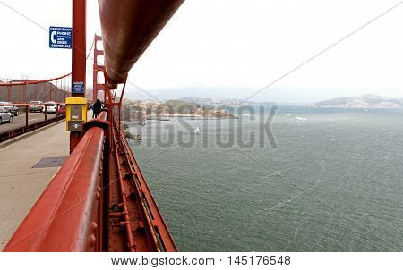 San Francisco,California-USA,August 2016:A view of the portion of the roadway and the sidewalk on the Golden Gate Bridge and the bay and the other side of the foggy morning in San Francisco,August 2016Editorial. Horizontal view.