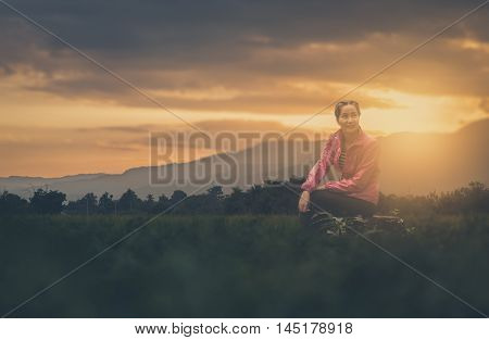 Vacation lifestyle scene of woman wearing sport cloths sitting on rocks with nature view in blurry background in morning time. Woman activity on holiday concept with vintage filter effect