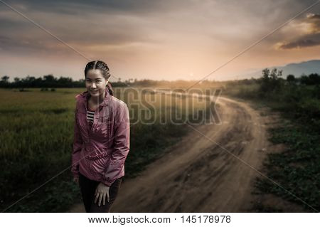 Vacation lifestyle scene of woman wearing sport cloths syanding beside canal in morning time. Woman activity on holiday concept with low key light