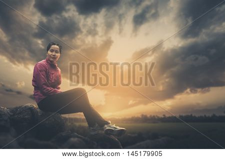 Vacation lifestyle scene of woman wearing sport cloths sitting on rocks with nature view in blurry background in morning time. Woman activity on holiday concept