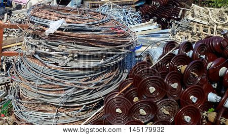 stacks of old power cable coils and insulators in a salvage yard, Songkhla, Thailand