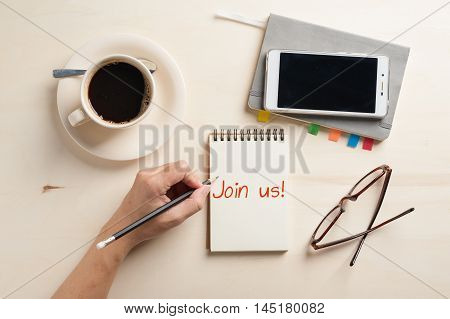 """Join us"" is written on notebook on wood table with coffee cup smartphone and glasses beside in morning time"