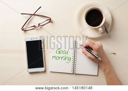 """""""Good morning"""" is written on notebook on wood table with coffee cup smartphone and glasses beside in morning time"""