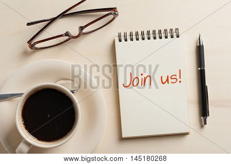 """Join us"" is written on opened notebook with blank area pen glasses and coffee cup on wood table in morning time"