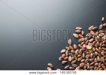 The roasted cocoa beans on black background.