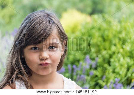 Portrait of attractive little girl outdoors. Little girl with pursed lips is looking at the camera