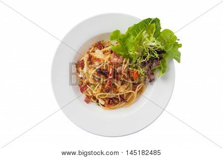 Top view of Thai Japanese and European fusion food style spicy pasta with bacon and dried chili in ceramic dish isolated on white background