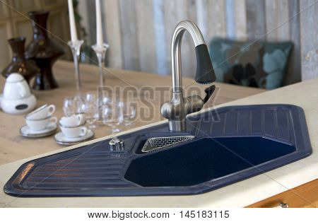 close up of blue kitchen sink and dining room table with dishes