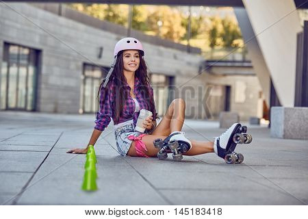 Young woman have a rest after rollerblading and drinking coffee on the urban city park. Happy teenager on rollerblading sitting on street a sunny day. Active lifestyle.