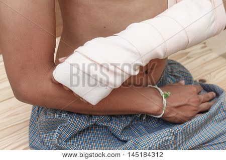 gauze bandage elastic. Pain and injury concept. Young man holds bandaged hand. Injured part of body. Medicine and healthcare.